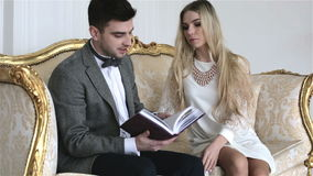 Een jong aantrekkelijk paar zit op een uitstekende bank en kijkt door een boek stock videobeelden