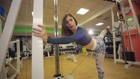 Een jong atletisch meisje die een oefening in een oversteekplaats in de gymnastiek doen stock videobeelden