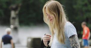 Een jong blond meisje met een fiets stijgt haar rugzak op en neemt een mobiele telefoon stock videobeelden