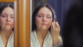 Een jong brunette in een witte laag voor een spiegel past kosmetische schaduwen op haar oogleden met een borstel toe stock videobeelden
