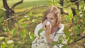 Een jong die meisje in een merinosplaid wordt verpakt verwarmt zich met thee van een mok van thermosflessen stock footage