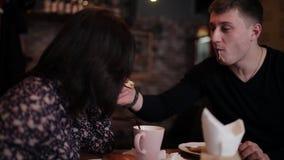 Een jong die paar samen door handcuffs Ontbijt in de koffie wordt geketend stock videobeelden