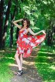 Een jong donkerbruin meisje in een rode kleding danst op een weg in een de zomerpark tegen een achtergrond van bomen Stock Fotografie