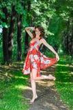 Een jong donkerbruin meisje in een rode kleding danst op een weg in een de zomerpark tegen een achtergrond van bomen Royalty-vrije Stock Foto's