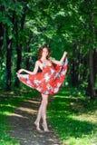 Een jong donkerbruin meisje in een rode kleding danst op een weg in een de zomerpark tegen een achtergrond van bomen Stock Afbeelding