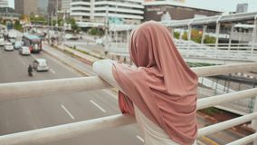 Een jong, droevig Moslimmeisje bevindt zich op een brug over het verkeer in Djakarta van de binnenstad indonesië Video in motie stock videobeelden