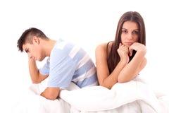 Een jong droevig paar in bed dat problemen en cris heeft Stock Foto