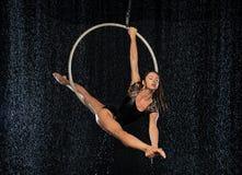 Een jong flexibel meisje voert de spleten in de luchtring uit Aqua Studio die prestaties op een zwarte achtergrond schieten royalty-vrije stock foto