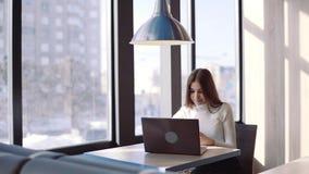 Een jong freelancermeisje zit in een koffie gebruikend laptop voor het verre werk stock footage