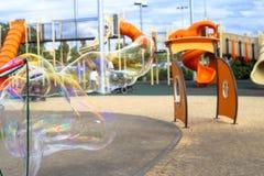 Een jong geitje maakt grote zeepbels in een speelplaats in Tel Aviv Stock Fotografie