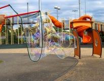Een jong geitje maakt grote zeepbels in een speelplaats in Tel Aviv op een bewolkte dag Stock Foto's