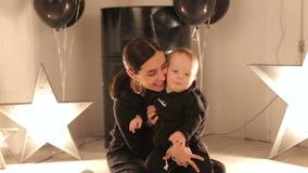 Een jong gelukkig mamma speelt met haar één éénjarigejongen in een studio met sterren stock footage