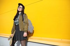 Een jong hipstermeisje berijdt een skateboard Meisjesmeisjes F stock afbeelding