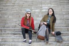 Een jong hipstermeisje berijdt een skateboard Meisjesmeisjes F stock fotografie