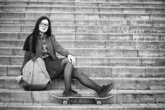 Een jong hipstermeisje berijdt een skateboard Meisjesmeisjes F stock foto's