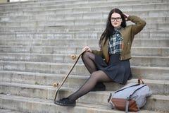 Een jong hipstermeisje berijdt een skateboard Meisjesmeisjes F royalty-vrije stock afbeelding