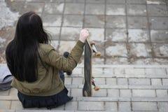 Een jong hipstermeisje berijdt een skateboard Meisjesmeisjes F royalty-vrije stock fotografie