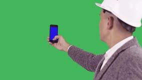 Een jong hoofd in een bouwhelm houdt een mobiele telefoon met het blauw scherm stock footage