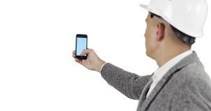 Een jong hoofd in een bouwhelm houdt een mobiele telefoon met het blauw scherm stock videobeelden