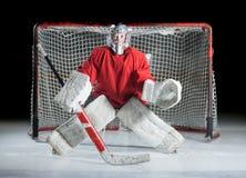 Een jong ijshockey goaltender in een klaar positie tegen dark royalty-vrije stock afbeeldingen