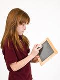 Jong schoolmeisje die op schoolbord schrijven stock foto's