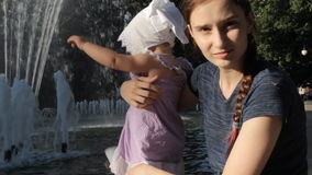 Een jong kindermeisje die een baby houden door een fontein stock video