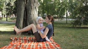 Een jong kindermeisje die een babymeisje in haar overlapping zetten en haar wiegen op een deken stock videobeelden