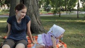 Een jong kindermeisje die een babymeisje neer op een deken zetten Het babymeisje kruipt weg stock video
