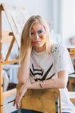 Een jong kunstenaarsmeisje met een gezicht en kleren in de verf stock foto's