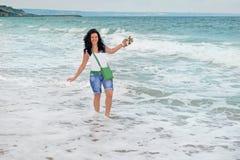 Een jong langharig meisje bevindt zich onder de golven in het overzees wit overzees schuim op de kust van de Zwarte Zee in Bulgar royalty-vrije stock fotografie