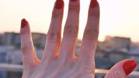 Een jong meisje bekijkt de zon door uw vingers stock videobeelden