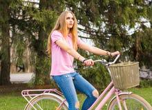 Een jong meisje berijdt op een fiets op de weg in het park Royalty-vrije Stock Foto's