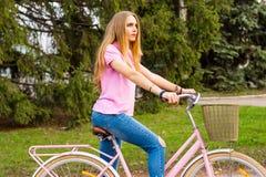 Een jong meisje berijdt op een fiets op de weg in het park Royalty-vrije Stock Afbeelding