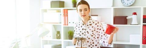 Een jong meisje bevindt zich in het bureau dichtbij de lijst, houdt een ketel in haar hand en houdt een kop stand stock afbeeldingen