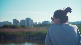 Een jong meisje bevindt zich op de kust van het meer tegen de achtergrond van het stedelijke landschap en de blauwe hemel stock videobeelden