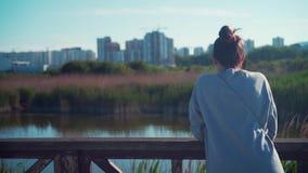 Een jong meisje bevindt zich op de kust van het meer tegen de achtergrond van het stedelijke landschap en de blauwe hemel stock video