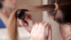 Een jong meisje bevindt zich voor een spiegel en kamt haar lang haar en doet een hoge staart stock video