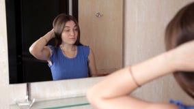 Een jong meisje bevindt zich voor een spiegel en verwierp haar haar met een staart stock video