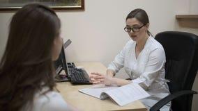 Een jong meisje bij de benoeming van een arts De arts schrijft behandeling aan de patiënt voor stock video