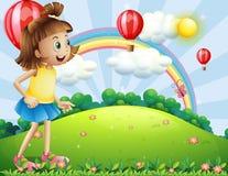 Een jong meisje bij de heuveltop die op de drijvende ballons letten Stock Foto