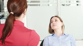 Een jong meisje bij een overleg met een tandartsvrouw in glazen zit op een stoel in een stamotologybureau E stock videobeelden
