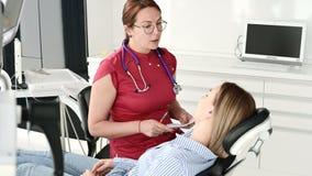 Een jong meisje bij een overleg met een tandartsvrouw in glazen zit op een stoel in een stamotologybureau E stock video