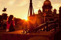 Een jong meisje bij zonsondergang op de achtergrond van St Isaac& x27; s Cathedra Royalty-vrije Stock Foto's