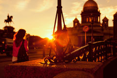 Een jong meisje bij zonsondergang op de achtergrond van St Isaac& x27; s Cathedra Stock Foto