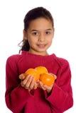 Een jong meisje dat kijker met 3 sinaasappelen aanbiedt stock foto's