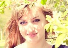 Een jong meisje in de gebloeide tuin Stock Foto