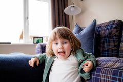 Een jong meisje die bij de camera in het huis gillen stock foto
