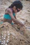 Een jong meisje die in de zand en de bouwkastelen spelen stock foto's