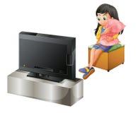 Een jong meisje die een hoofdkussen koesteren terwijl het letten van op TV Stock Afbeelding