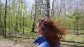 Een jong meisje die een ochtend doen stoot in het Park aan Meisje die aan muziek door hoofdtelefoons luisteren Gezonde Levensstij stock video